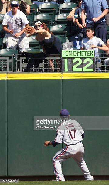 A fan catches a home run ball hit by Ichiro Suzuki of the Seattle Mariners as Right Fielder Shinsoo Choo of the Cleveland Indians watches on July 19...