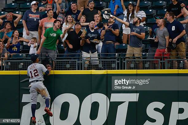 Fan catches a three-run home run off the bat of Logan Morrison of the Seattle Mariners as Center fielder Anthony Gose of the Detroit Tigers watches...