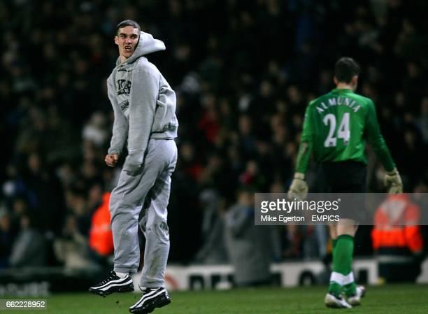 A fan celebrates Blackburn Rovers victory on the pitch as Arsenal's goalkeeper Manuel Almunia walks off dejected