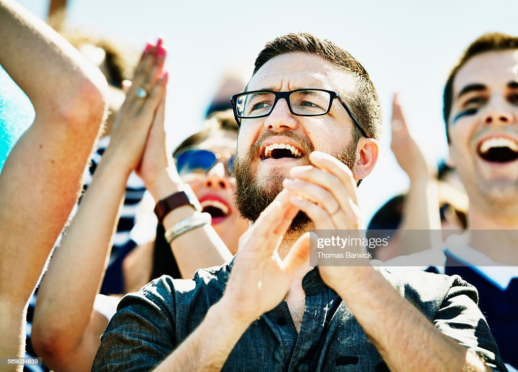 Fan celebrating during football game in stadium : Stock Photo