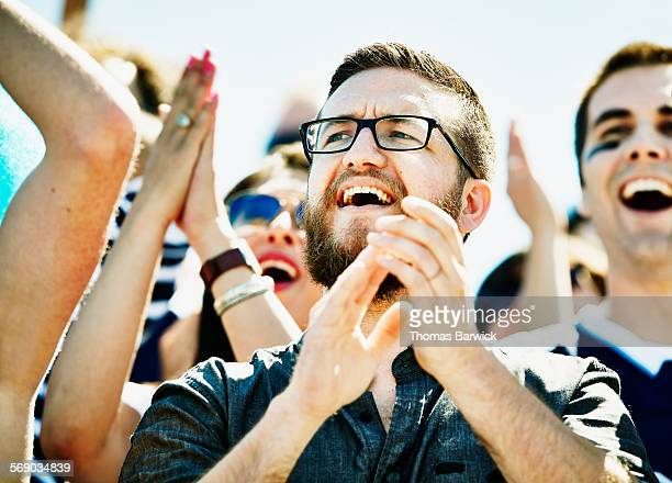 Fan celebrating during football game in stadium