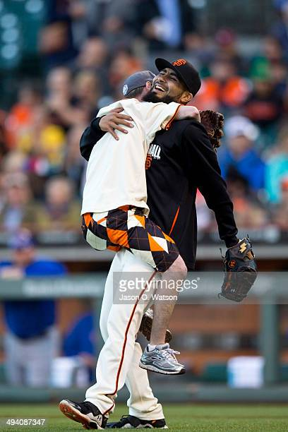 Fan Charlie Hughes hugs Sergio Romo of the San Francisco Giants after throwing out the ceremonial first pitch before the game against the Chicago...