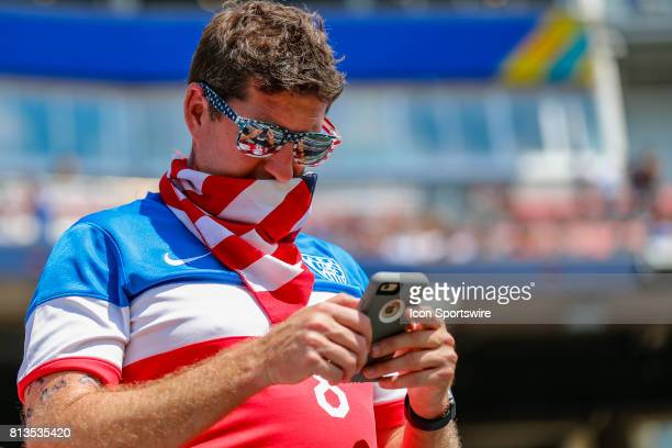 A US fan checks his cell phone prior to the 11 draw between the United States and Panama on July 08 2017 in the opening round CONCACAF Gold Cup game...