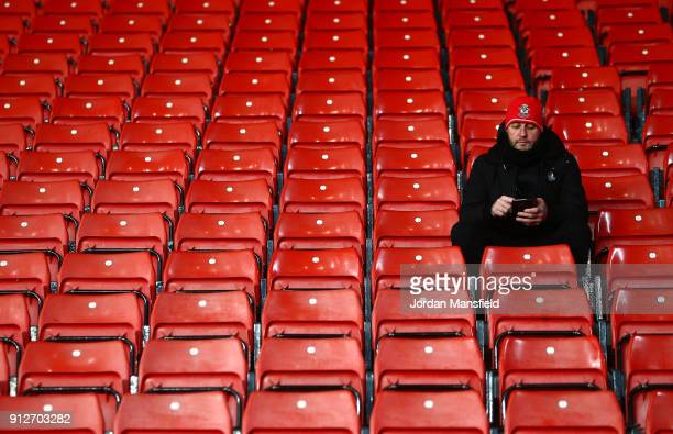 A fan checks his phone prior to the Premier League match between Southampton and Brighton and Hove Albion at St Mary's Stadium on January 31 2018 in...