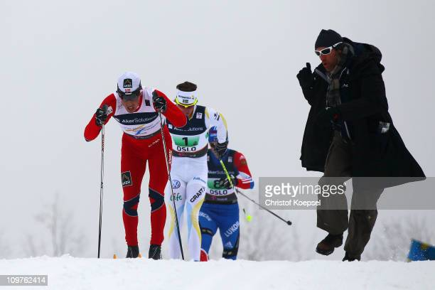 A fan cheers on Eldar Roenning of Norway Johan Olsson of Sweden and Stanislav Volzhentsev of Russia in the Men's Cross Country 4x10km Relay race...