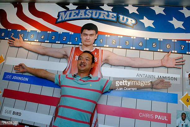 A fan compares his arm span to a likeness of Yao Ming of the Houston Rockets at the NBA Jam Van on June 6 2007 at Universal City Walk in Universal...