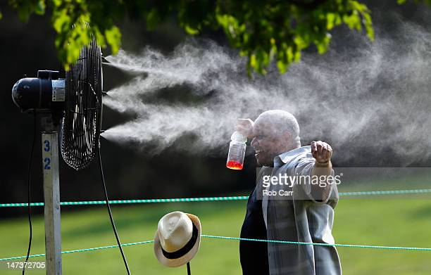 A fan cools off in a misting maching beside the 16th hole during Round One of the ATT National at Congressional Country Club on June 28 2012 in...