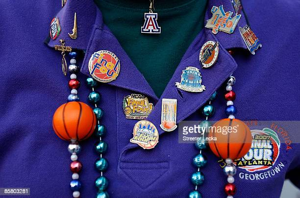A fan covered with pins from previous Final Fours poses for a picture before the National Semifinal games of the NCAA Division I Men's Basketball...