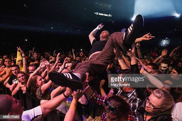 A fan crowd surfsas Papa Roach performs on stage at Xfinity Arena on September 12 2015 in Everett Washington
