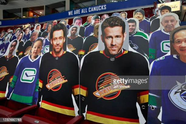 Fan cutouts of actors Hugh Jackman and Ryan Reynolds sit in the stands before the NHL game between the Vancouver Canucks and the Edmonton Oilers at...