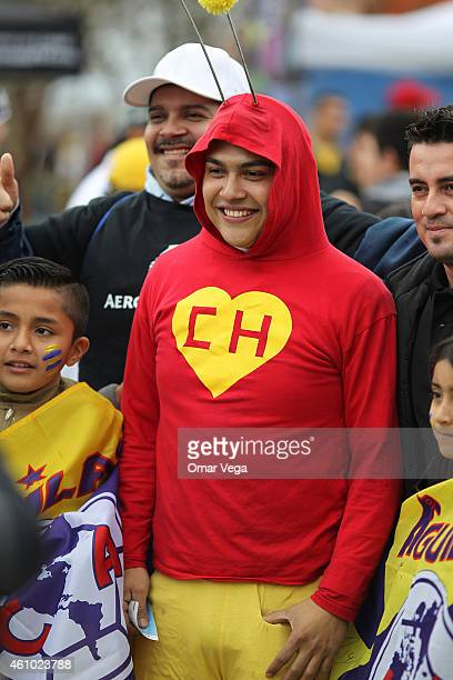 A fan disguised as a character of a famous Mexican serie named as Chapulin Colorado smiles during a friendly match between America and Monterrey at...