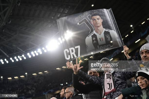 A fan displays a poster of Juventus' Portuguese forward Cristiano Ronaldo prior to the UEFA Champions League round of 16 secondleg football match...