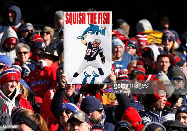A fan displays a sign during a game between the New England Patriots and the Miami Dolphins at Gillette Stadium on November 26 2017 in Foxboro...