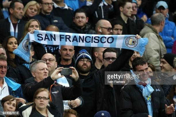 A fan displays a team scarf during the Premier League match between Manchester City and Manchester United at Etihad Stadium on April 7 2018 in...