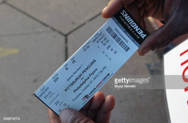 A fan displays opening night tickets for the game between the Pittsburgh Penguins and the Philadelphia Flyers at the Consol Energy Center on October...