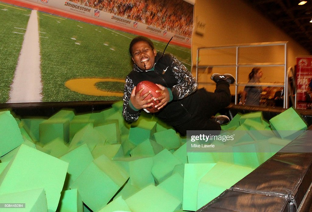 A fan dives into a foam pit to catch a football at the Moscone Center West prior to Super Bowl 50 on February 4, 2016 in San Francisco, United States.