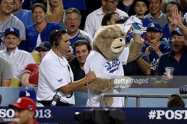 Fan dressed as a bear is escorted out of the stadium for dancing on the St. Louis Cardinals dugout in the eighth inning as the Cardinals take on the...