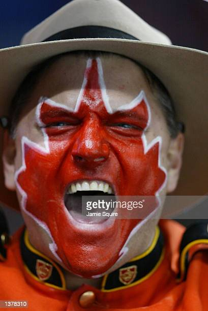 A fan dressed as a Royal Canadian Mounted Policeman wears a red maple leaf with white trim painted on his face as he screams for Canada during the...