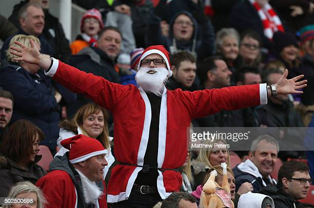 A fan dressed as Father Christmas watches from the stands during the Barclays Premier League match between Stoke City and Manchester United at...