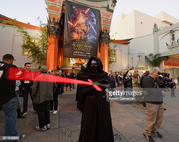 A fan dressed as Kylo Ren waves his light saber before the opening night of Walt Disney Pictures and Lucasfilm's Star Wars The Force Awakens at TCL...