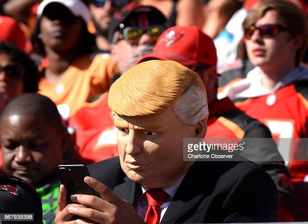 A fan dressed as President Donald Trump keeps his fingers moving on his iPhone during the Carolina Panthers against Tampa Bay Buccaneers game on...