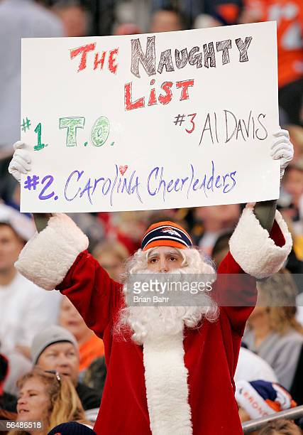 A fan dressed as Santa Claus shows his naughty list during a game between the Denver Broncos and the Oakland Raiders on December 24 2005 at Invesco...