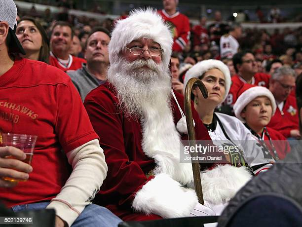A fan dressed as Santa Claus wtaches a game between the Chicago Blackhawks and the San Jose Sharks at the United Center on December 20 2015 in...