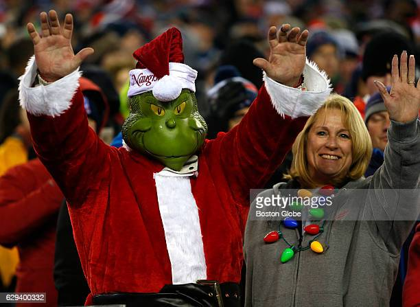 A fan dressed as the Grinch in a Santa suit watches the game New England Patriots play against the Baltimore Ravens at Gillette Stadium in Foxborough...