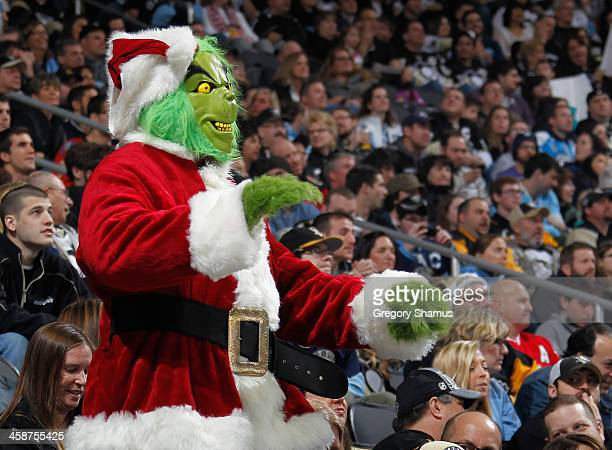 A fan dressed as the Grinch watches the Pittsburgh Penguins during the first period against the Calgary Flames on December 21 2013 at Consol Energy...