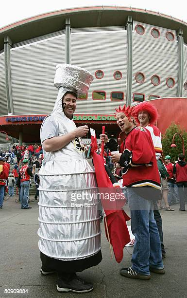 A fan dressed as the Stanley Cup and other Calgary Flames fans gather outside of the arena before the start of game three of the NHL Stanley Cup...