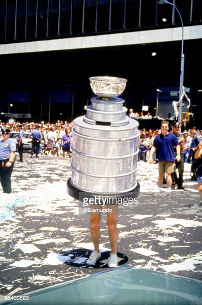 A fan dressed as the Stanley Cup stands in the tickertape filled street during a Parade to celebrate the New York Rangers defeat of the Vancouver...