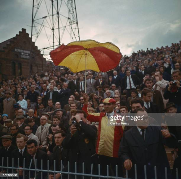 A fan dressed in Spanish colours and holding a matching umbrealla supporting his national team at Villa Park during the 1966 World Cup in England...