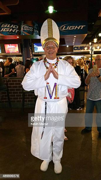 A fan dressed like the Pope watches Madonna perform onstage during her 'Rebel Heart' tour at Wachovia Center on September 24 2015 in Philadelphia...