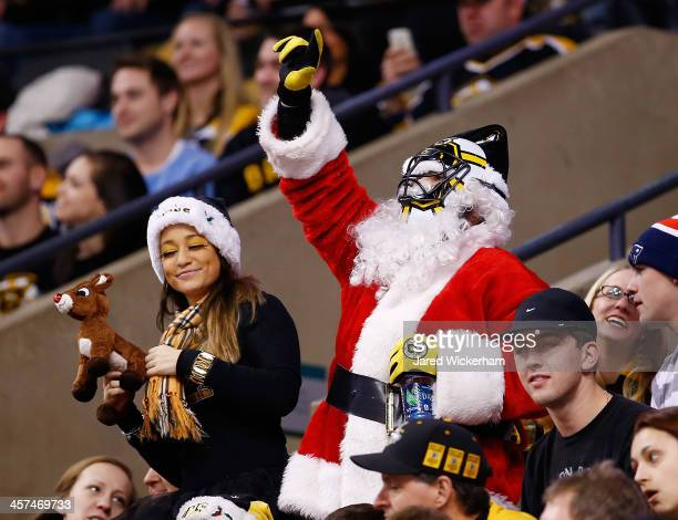 A fan dressed up as Santa Claus wears a Boston Bruins hockey mask in the third period during the game against the Calgary Flames at TD Garden on...
