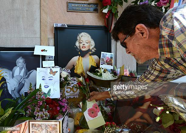 Fan Eric Woodard from Florida leaves roses at the crypt of Marilyn Monroe before a memorial service to mark the 50th anniversary of the Hollywood...