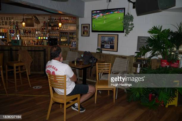 Fan finds a quiet corner to watch the match on his own during the UEFA Euro 2020 Championship Final between Italy and England at Fistral Beach Bar on...