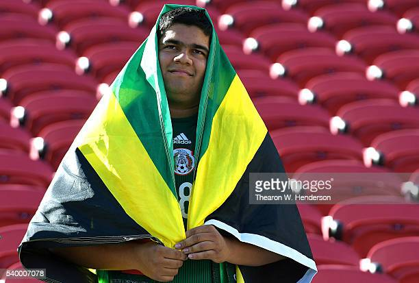 A fan for Jamaica wears the Jamaican flag prior to the start of the 2016 Copa America Centenario Group match play between Uruguay and Jamaica at...