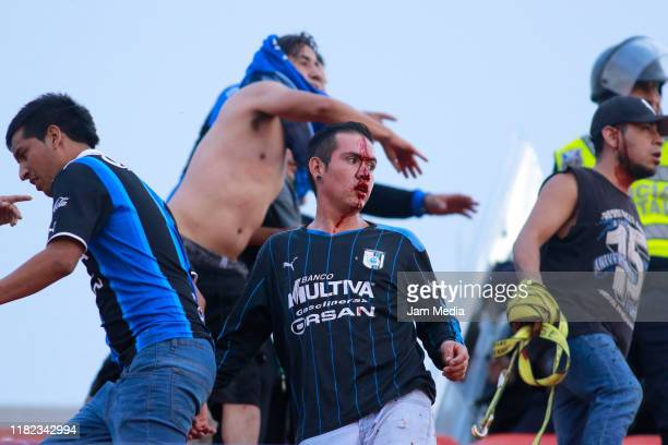 A fan from Queretaro react while bleeding when fans of San Luis and Queretaro started a fight between them in the stands during the 14th round match...