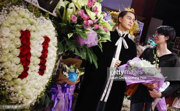 A fan from the mainland of late Cantopop Leslie Cheung Kwokwing offers wreaths next to Cheung's wax figure at Madame Tussauds Hong Kong the Peak on...