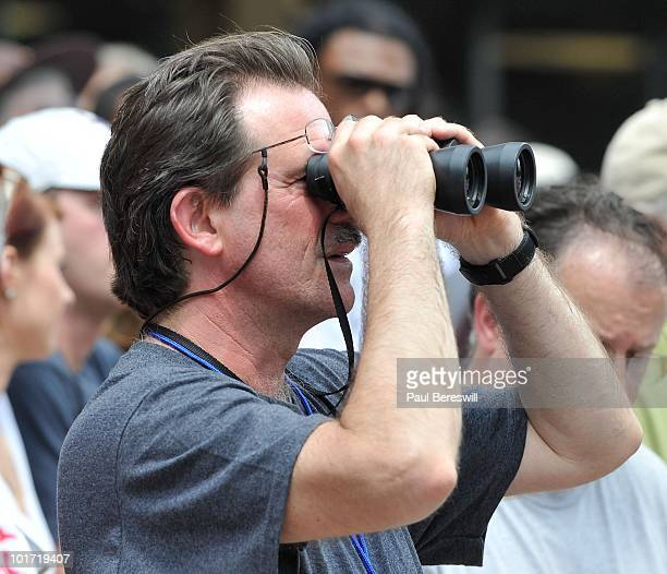 A fan gets a closer look at the horses as he looks through binoculars at the paddock area before a race at the running of the 142nd Belmont Stakes at...