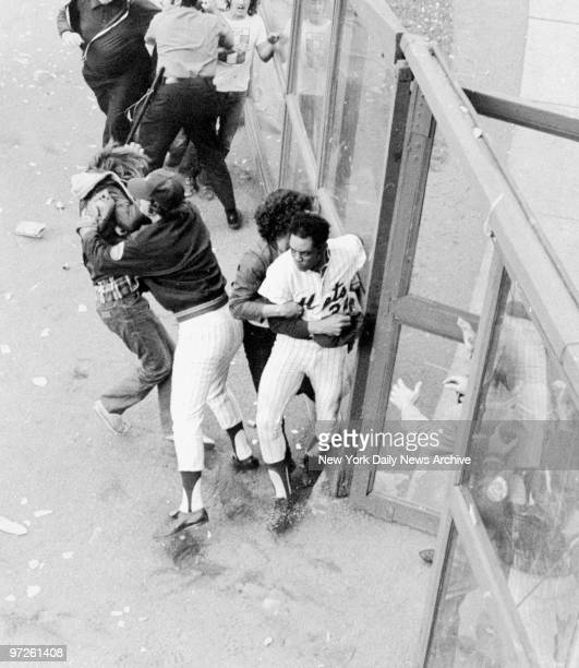 Fan grabs New York Mets' Willie Mays in right field as another player from the bullpen grabs a fan at Shea Stadium