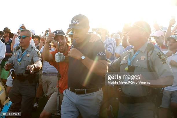 Fan grabs Phil Mickelson of the United States and gives him a thumbs up as he walks up the 18th fairway after playing an approach shot during the...