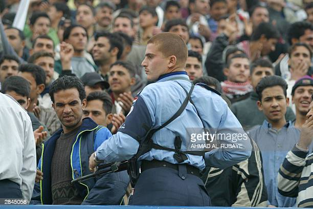 A fan grimaces as he looks at the weapon of an Iraqi policeman during the final between rival Baghdad clubs alZawra and alTalaba of the Baghdad Cup...