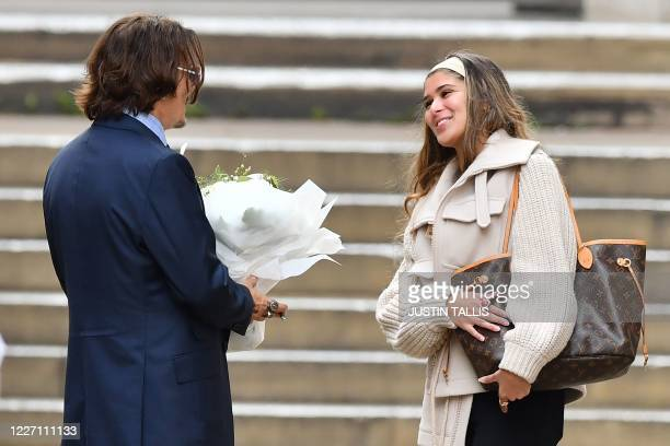 Fan hands a bunch of flowers to US actor Johnny Depp as he leaves court after the sixth day of his libel trial against News Group Newspapers , at the...
