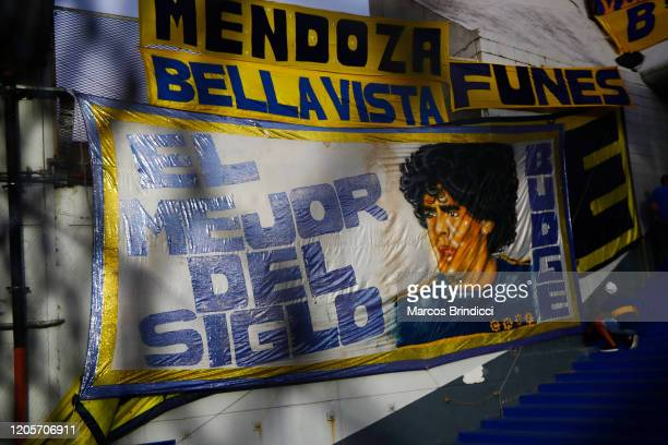 A fan hangs a flag with an image of Diego Maradona former Boca Juniors player and coach of Gimnasia y Esgrima La Plata before a match between Boca...