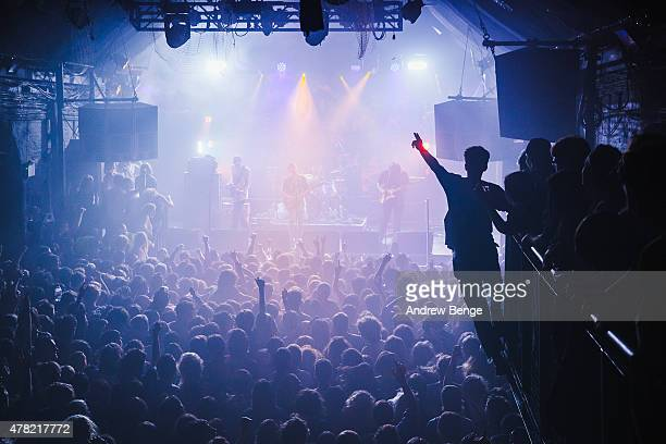 A fan hangs off the balcony whilst Fidlar perform on stage at Heaven on June 23 2015 in London United Kingdom