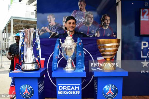 A fan has his photo taken with the 3 trophies that PSG won last season before the International Champions Cup match between Paris Saint Germain and...