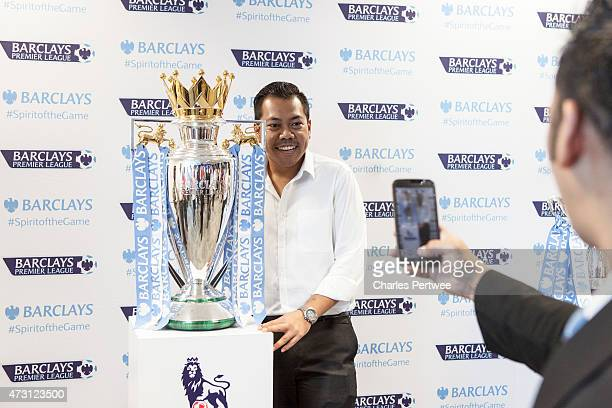A fan has his photo taken with the Barclays Premier League trophy during a QA at the Barclays office during the Barclays Asia Trophy 2015 Ticket...