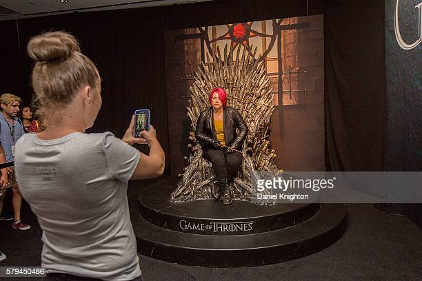 A fan has their photo taken on the Iron Throne from HBO's hit series Game of Thrones at ComicCon International Day 3 on July 22 2016 in San Diego...