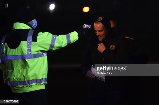 Fan has their temperature checked by a member of staff wearing a PPE prior to entering the stadium ahead of the Sky Bet League One match between...